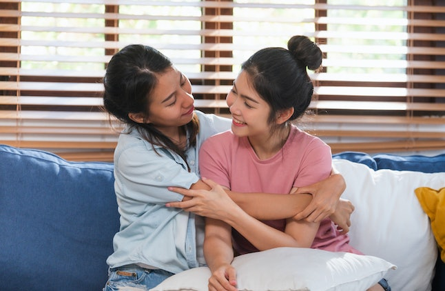 Happy asian lesbian couple hug each other with love on sofa at living room at home,LGBTQ lifestyle concept