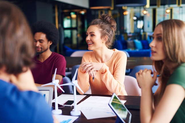 Young coworkers talking at conference table