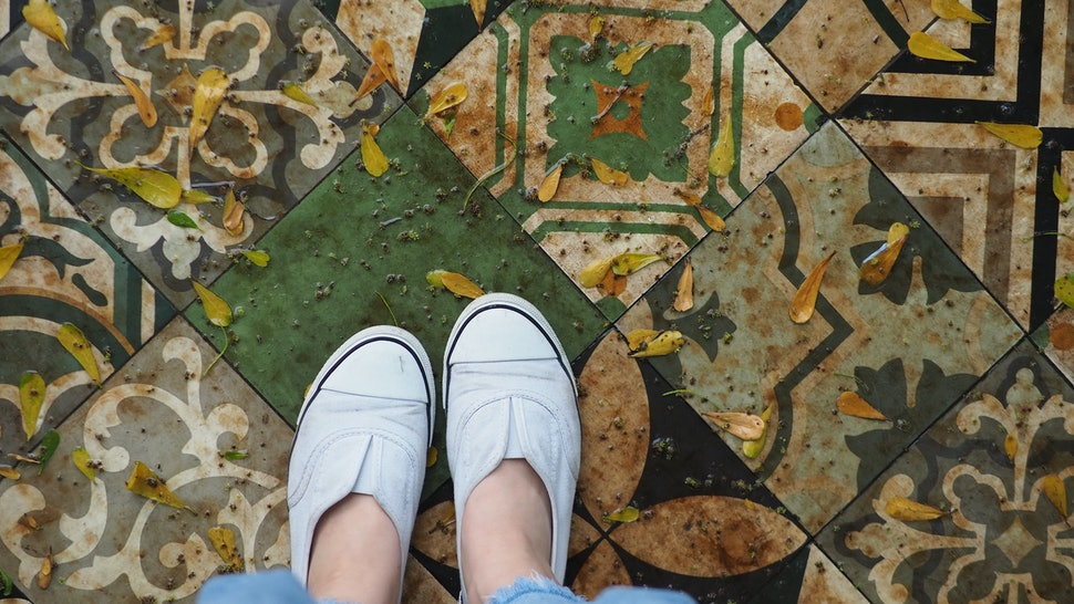 Women in casual white shoes and jeans stand on a Moroccan tile. Yellow leaves fall over wet area after rain, rainy season background.