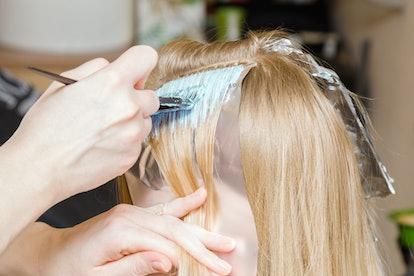 Hairdresser hands bleaching strands of blonde woman hair in beauty salon. Closeup.