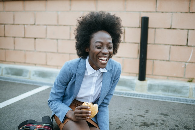 Black young woman drinking a soda and eating hamburguer sitting on the floor of a parking lot