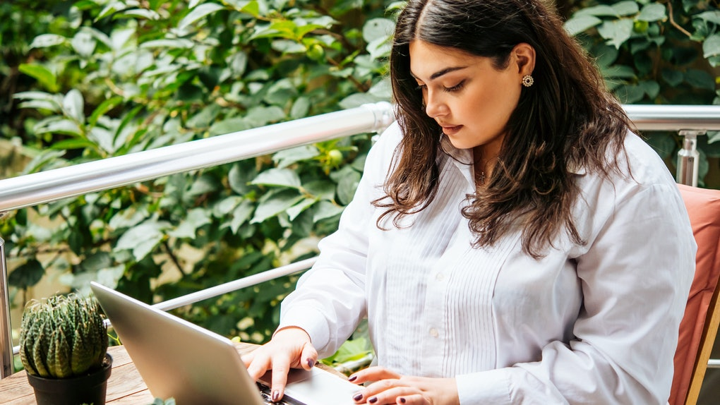 Portrait of beautiful plus size girl working on her laptop on balcony or terrace of cafe