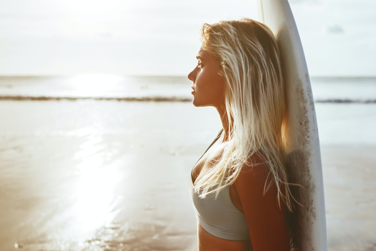Surfer girl surfing looking at ocean beach sunset summer time