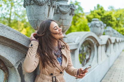 Young happy smiling girl using modern smartphone outdoors, beautiful woman texting sms message via her cellphone while walking at the park in the city. Woman  texting on the smart phone