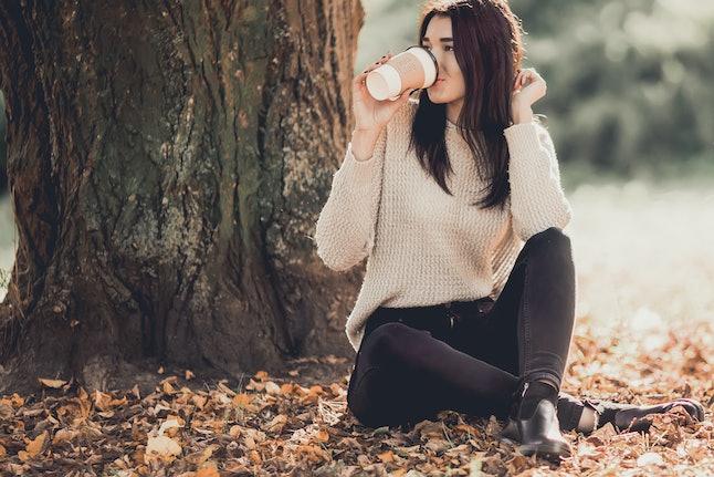 Beautiful woman drink coffee sitting in autumn park.