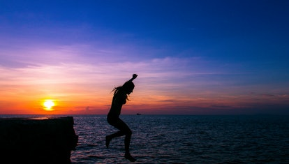 Silhouette of scared woman in the air falling from cliff into water at lovely colorful sunset in the...