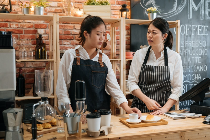 two emotional waitresses colleagues arguing with customer meal on counter table. coffee shop barista not satisfied with coworkers work of beverage and croissant. frowning woman talking and redo order