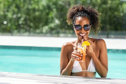 Portrait of happy fashion woman with sunglasses standing in swimming pool drinking cocktail. Beautif...