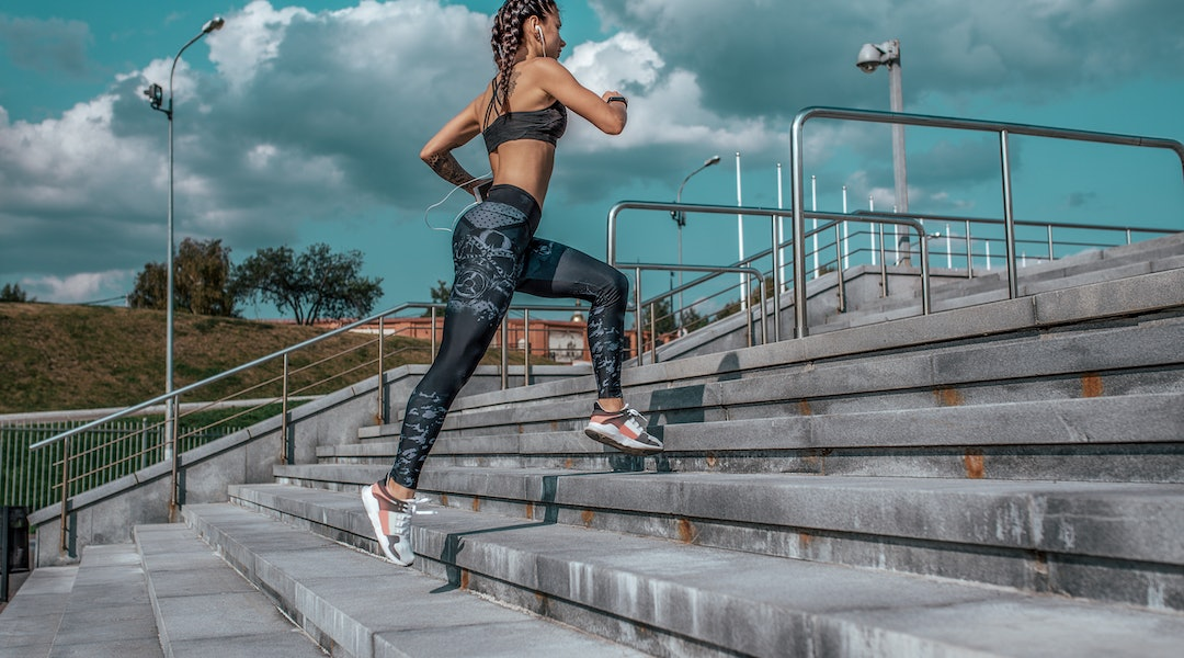 A person runs up some outdoor city stairs. Mixing up your workout routine is essential for keeping your mind and body engaged.