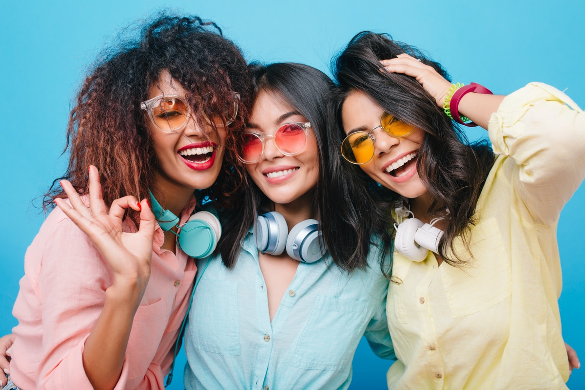 Close-up portrait of excited three girls laughing on blue background during meeting. Indoor photo of good-looking ladies in colorful sunglasses enjoying free time together.