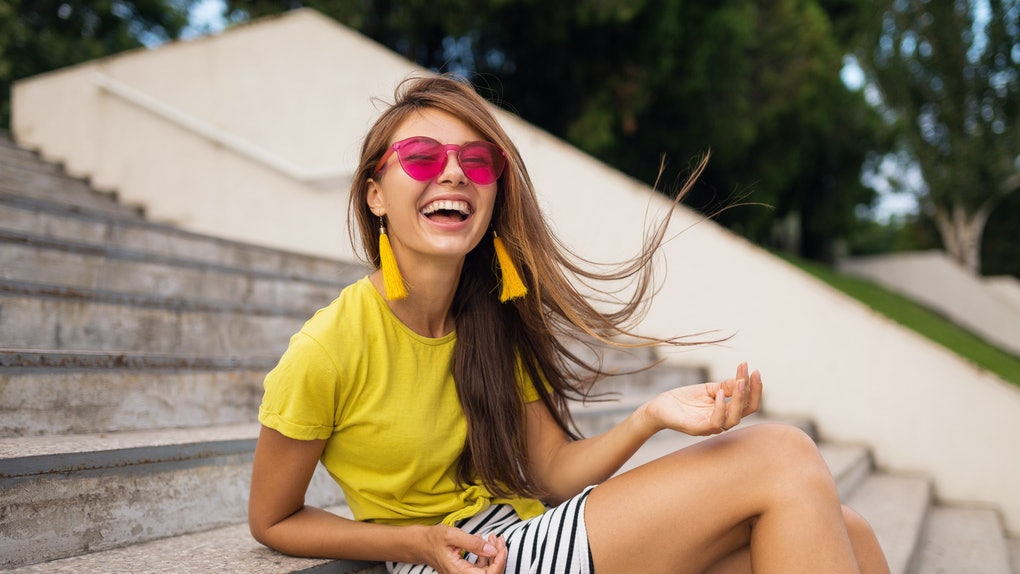 young attractive stylish smiling woman having fun in city park, positive, emotional, long hair, wearing yellow top, striped mini skirt, pink sunglasses, summer style fashion trend,