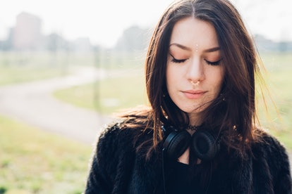 Half length of young beautiful caucasian  woman with headphones around her neck, eyes closed - serene, relaxed, thinking future concept