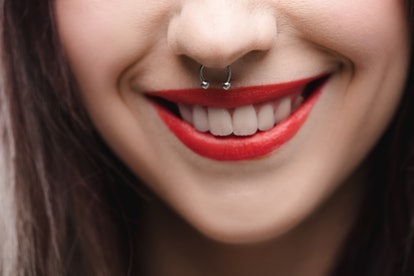 close up view of young girl with red lips and piercing in nose
