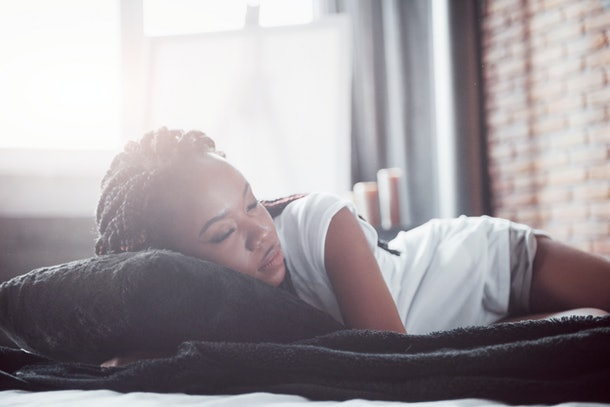 A beautiful African woman lies and sleeps in bed, in a white bedroom. Good morning, vacation at home. The girl is wearing a T-shirt, pigtails on her head.