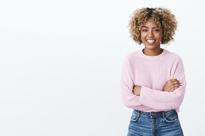 Cute african-american girl entertained with funny conversation standing relaxed and carefree with hands crossed over body smiling friendly at camera as talking, wearing warm purple trendy sweater