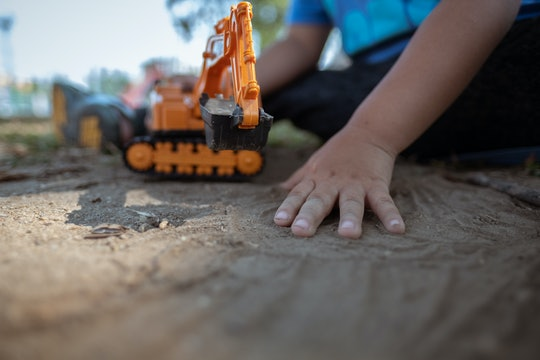 close up image of kid hands holding plastic tractor toy playing on dirt ground
