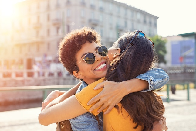 Happy meeting of two friends hugging in the street. Smiling girls friends laughing and hugging in the city centre. Multiethnic young women embrace each others after long time they have been distant.