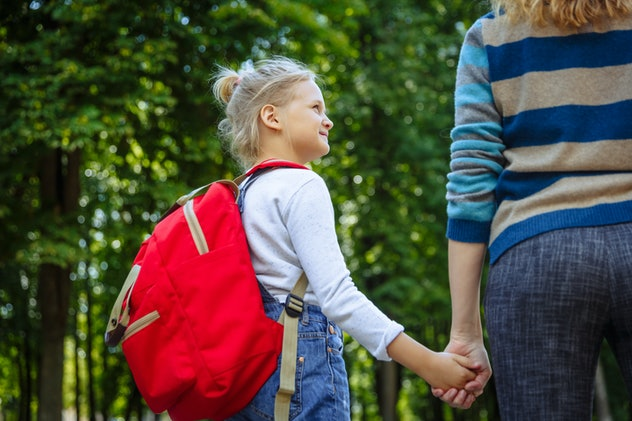 First day at school. Woman and girl with red backpack behind the back. Beginning of lessons. First day of fall. Back to school concept.