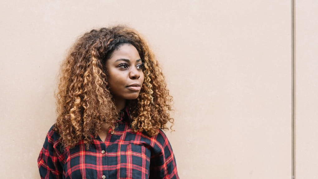 Portrait of young black woman wearing checked shirt looking away while standing against bright background