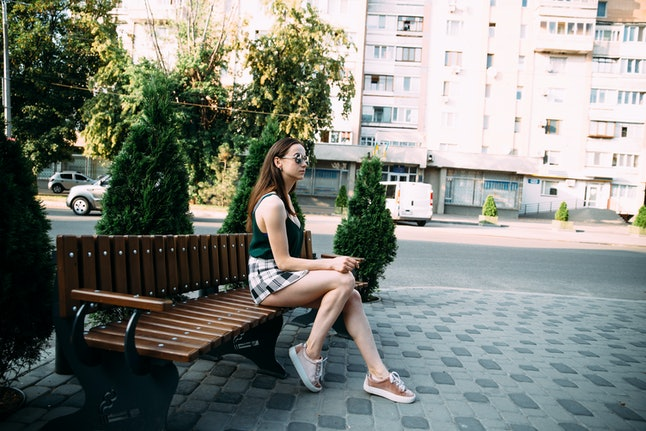 A girl in a black T-shirt and shorts in a park on a bench