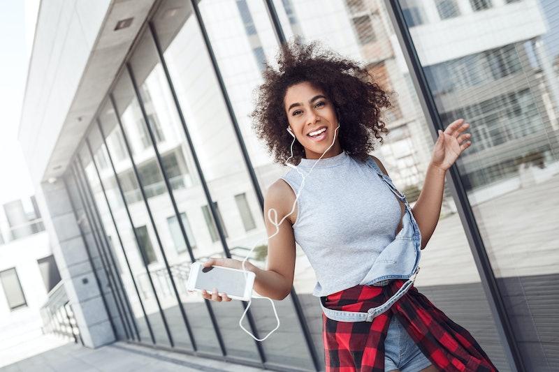 Young woman in the city street walking near window holding smartphone wearing earphones listening to...