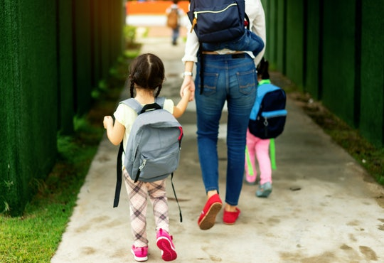 Mom and kids walking hand in hand into school