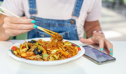 A person is eating a noodle dish with chicken, and scrolling on their phone. Harper says that during flares, pasta dishes are her favorite meals.