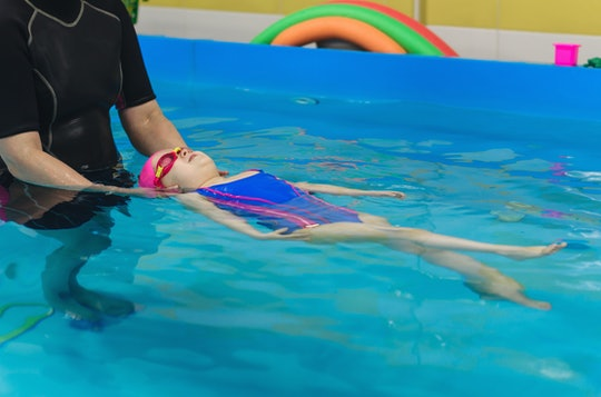 A little girl of European appearance in a pink rubber cap learning to swim in the pool