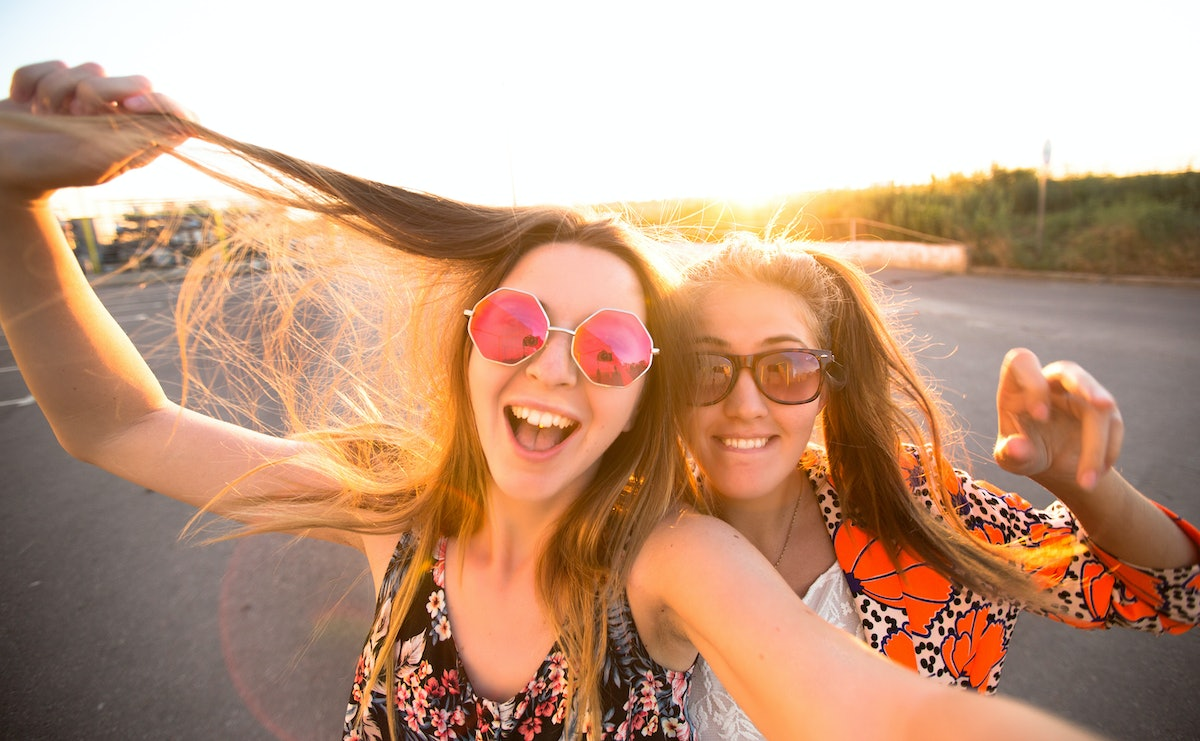 close-up lifestyle portrait of young best friends girls having fun at cool sunset.Travel concept,hap...