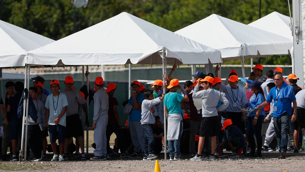 Migrant children stand outside the Homestead Temporary Shelter for Unaccompanied Children, in Homestead, Fla