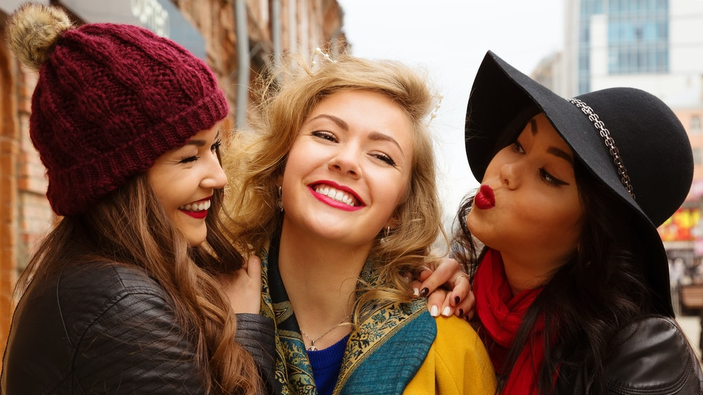 Young pretty  girls best friends smiling and having  fun, walking at the city. Shopping.  Wearing stylish outerwear. Bright make up. Positive emotions. Outdoors lifestyle fashion close up portrait
