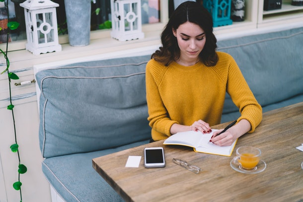 Young concentrated beautiful woman with brown hair in yellow sweater writing in notebook with empty white pages while sitting at wooden desk in cafe