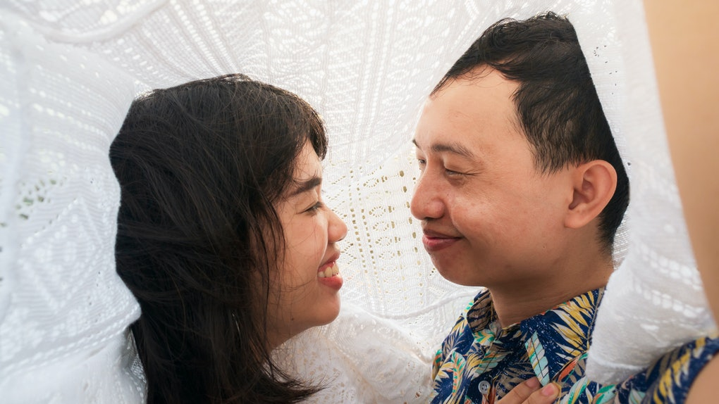 Young couple looking into each other's eyes. Romantic under lace fabric  seaside.