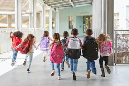 Elementary school kids run from camera in corridor, close up