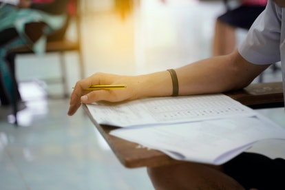 Student check Answer choice with pencil on optical form of standardized test answers bubbled score a...
