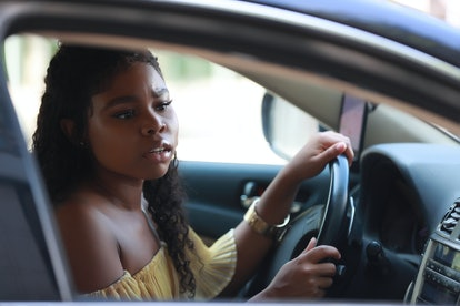 Pretty black woman driving car with caution and looking at mirror on side while steering