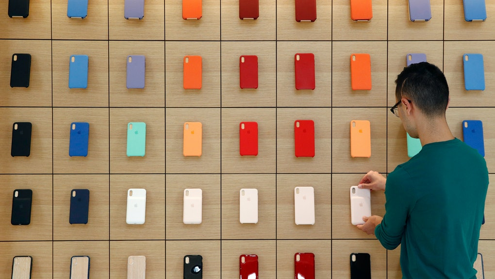 An Apple retail employee places a phone case on a display during a press preview of the new Apple Store inside the Carnegie Library, in Washington