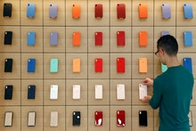 An Apple retail employee places a phone case on a display during a press preview of the new Apple St...