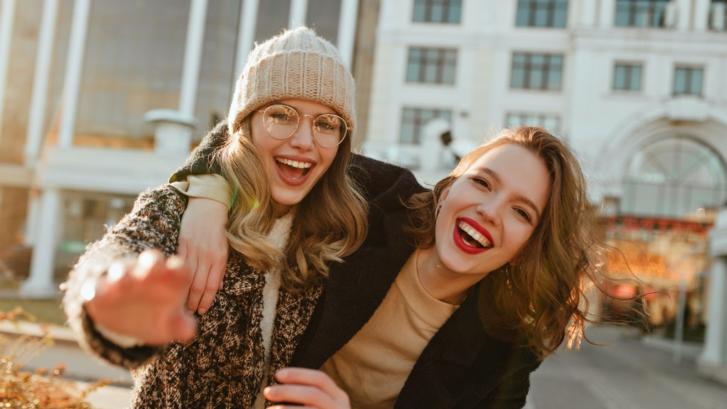 These cheerful women laughing and walking through the city in the fall are striking a great pose for fall puns for Instagram captions.