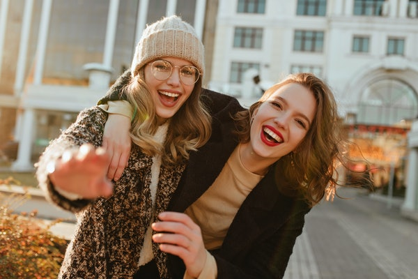 Two best friends laugh and take a picture while hanging out in the city in the fall.
