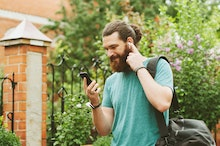 Cheerful happy bearded man looking at his smartphone, listening to the music with earpods outdoors.