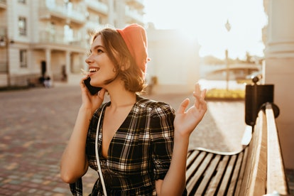 Positive female model in elegant clothes enjoying autumn day. Outdoor photo of gorgeous curly woman in red beret talking on phone.