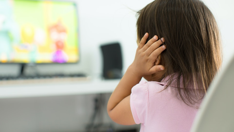 A terrified child, afraid of the loud sounds from the television. Autism.