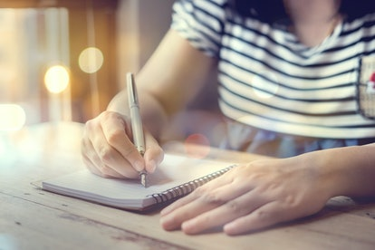 female hands with pen writing on notebook on wooden table