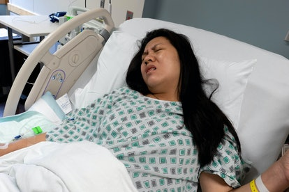Young Pregnant Asian Woman in Pain for Labor and Delivery inside Hospital