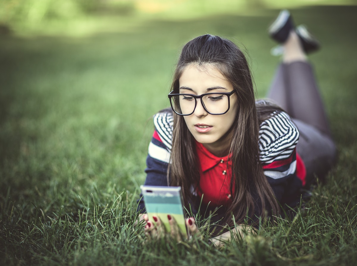 Beautiful young hipster girl using smart phone lying on the grass in the park