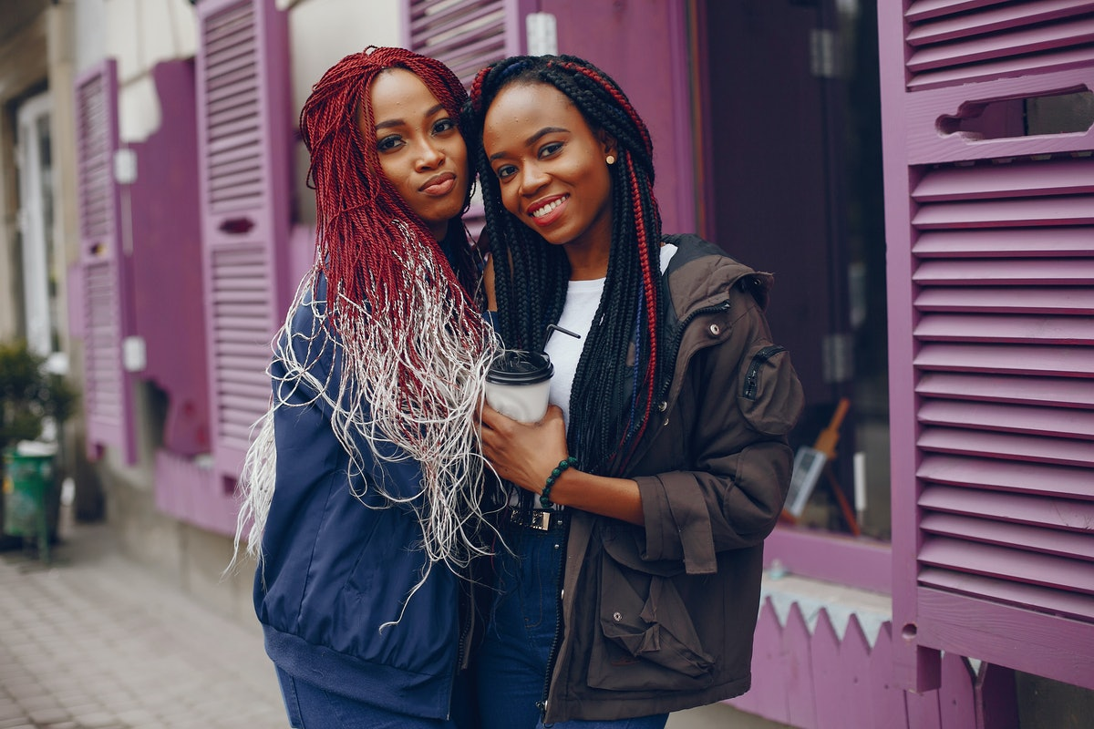 two beautiful and stylish dark-skinned girls with long hair standing in a autumn city near purple wa...