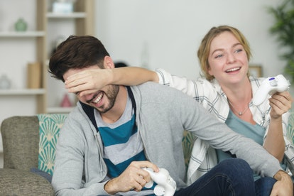 girlfriend covering boyfriends eyes and playing video game