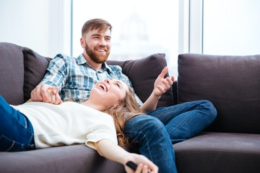 Portrait of a laughing couple having fun on the sofa at home