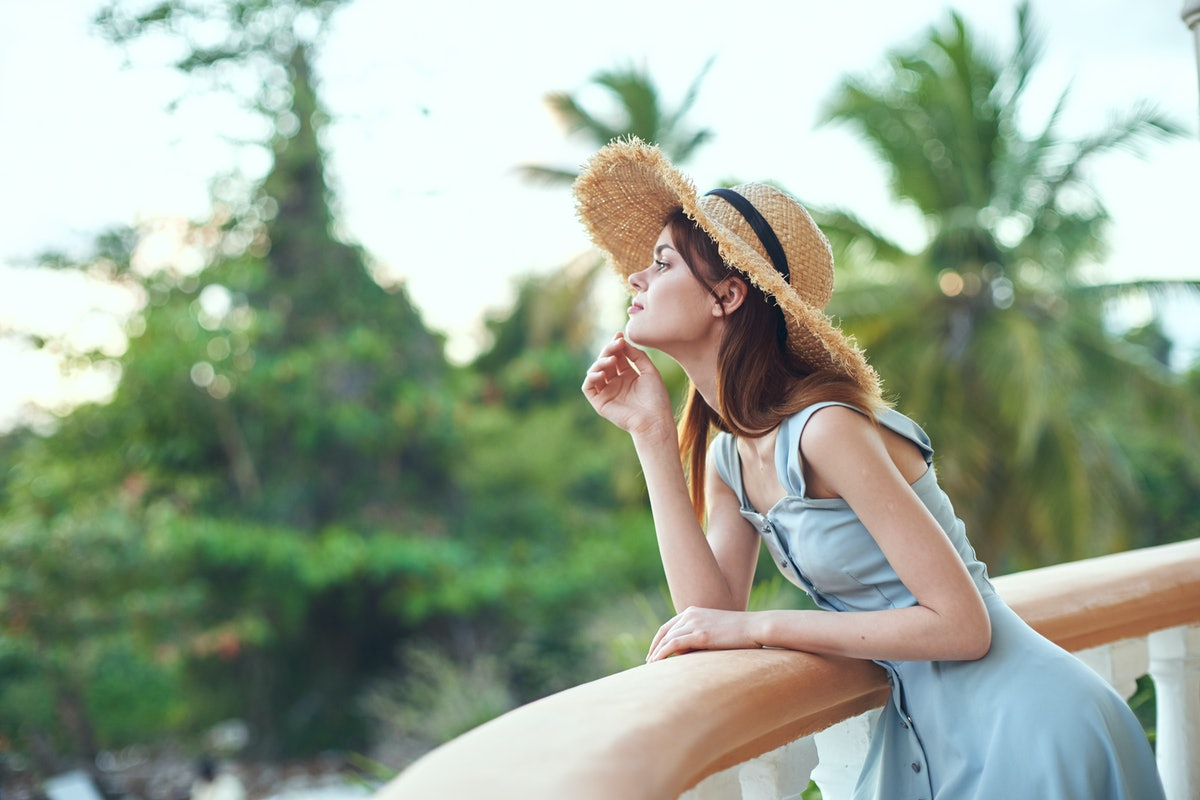 A dreamy woman in a sundress and a hat leaned on the balcony railing and looks at nature.